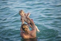 Enfant heureux avec le père en mer, un jeu d'amusement Image libre de droits