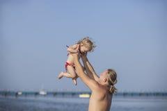 Enfant heureux avec le père en mer, un jeu d'amusement Photo libre de droits