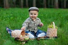 Enfant heureux avec le panier des fruits jouant dehors dans le pair d'automne Photos libres de droits