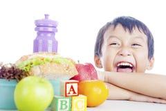 Enfant heureux avec le repas scolaire Photo stock