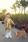 Enfant heureux ayant l'amusement avec la robe traditionnelle ao Dai dans l'Ochna dedans Image libre de droits