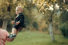 Enfant heureux ayant l'amusement Sourire mignon d'enfant en bas âge dans le costume, chemises, espadrilles sous l'arbre, mode Photographie stock