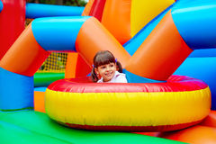 Enfant heureux, ayant l'amusement sur le terrain de jeu gonflable d'attraction Photographie stock libre de droits