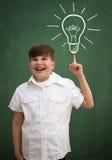 Enfant heureux contre le tableau noir avec dessiner l'idée d'ampoule Photographie stock libre de droits