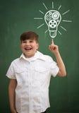 Enfant heureux contre le tableau noir avec dessiner l'idée d'ampoule Photographie stock