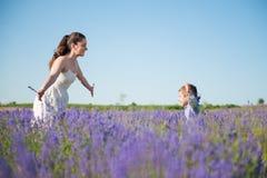 Enfant heureux courant dans les bras de la mère de sourire sur le gisement de fleur Photographie stock