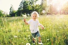 Enfant heureux courant sur le pré des fleurs Photographie stock libre de droits