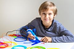 Enfant heureux créant le nouvel objet 3d avec le stylo de l'impression 3d Image stock