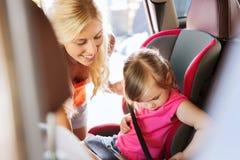 Enfant heureux d'attache de mère avec la ceinture de sécurité de voiture Image stock