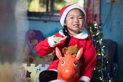 Enfant heureux dans le chapeau de Santa avec un cadeau près de l'arbre de Noël, ch Images libres de droits