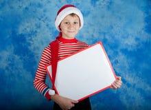 Enfant heureux dans le chapeau rouge de Santa tenant le conseil blanc Photos libres de droits