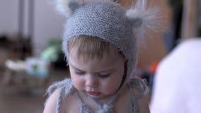 Enfant heureux dans le costume de bête avec des oreilles rongeant le hochet sur le fond unfocused clips vidéos