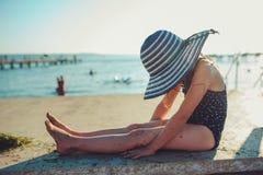 Enfant heureux dans le maillot de bain et le chapeau détendant sur la plage d'été et obtenant un certain bronzage Image libre de droits