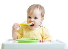 Enfant heureux de bébé s'asseyant dans la chaise avec une cuillère Images stock