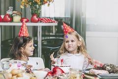 Enfant heureux de deux petites filles célébrant un anniversaire avec le gâteau à Photo libre de droits
