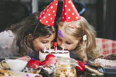 Enfant heureux de deux petites filles célébrant un anniversaire avec le gâteau à Image libre de droits