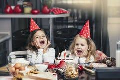 Enfant heureux de deux petites filles célébrant un anniversaire avec le gâteau à Photographie stock