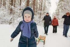 Enfant heureux de fille avec la promenade de famille dans la forêt neigeuse d'hiver Photographie stock