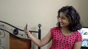 Enfant heureux de fille de Caucasien asiatique indien adorable mignon prenant le selfie faisant le tacaud au téléphone portable e clips vidéos