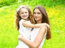 Enfant heureux de mère et de fille étreignant en été Photographie stock libre de droits