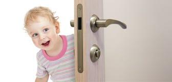Enfant heureux derrière la porte Photo stock