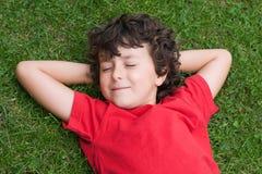 Enfant heureux en sommeil sur l'herbe Photo stock