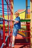 Enfant heureux escaladant le mur de corde, jouant des jeux sur le terrain de jeu coloré de château Image stock