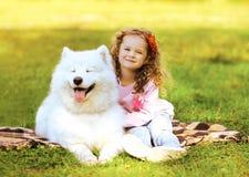 Enfant heureux et chien se reposant sur l'herbe photos libres de droits