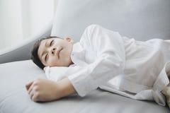 Enfant heureux heure du coucher dormant sur le sofa photographie stock
