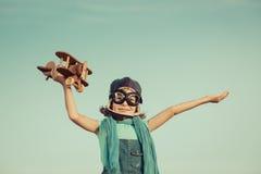 Enfant heureux jouant avec l'avion en bois de jouet Photographie stock libre de droits