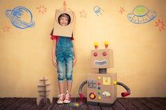 Enfant heureux jouant avec le robot de jouet Photo libre de droits