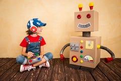 Enfant heureux jouant avec le robot de jouet Photo stock