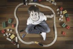 Enfant heureux jouant avec le train de jouets Garçon s'asseyant sur la fourmi en bois de plancher regardant l'appareil-photo et l Photos libres de droits