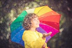 Enfant heureux jouant sous la pluie photos libres de droits