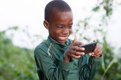 Enfant heureux jouant sur l'extérieur de téléphone dans le jour ensoleillé images libres de droits