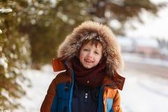 Enfant heureux marchant dans une forêt d'hiver dans le jour ensoleillé Photo stock