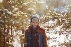 Enfant heureux marchant dans une forêt d'hiver dans le jour ensoleillé Photographie stock