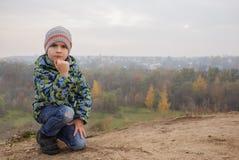 Enfant heureux mignon de garçon dehors Bois brumeux sur le fond Photographie stock libre de droits
