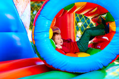 Enfant heureux mignon, garçon jouant dans l'attraction gonflable sur le terrain de jeu Photos libres de droits