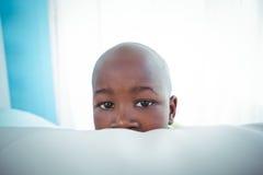 Enfant heureux regardant de derrière du divan Photos stock