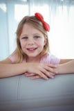 Enfant heureux regardant de derrière du divan Photographie stock