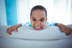 Enfant heureux regardant de derrière du divan Images libres de droits