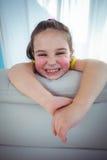 Enfant heureux regardant de derrière du divan Photos libres de droits