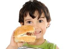 Enfant heureux retenant l'hamburger Photographie stock libre de droits
