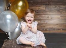 Enfant heureux s'asseyant sur une valise jouant et ayant l'amusement Photographie stock libre de droits