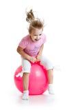 Enfant heureux sautant sur la boule de rebondissement image stock