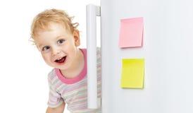 Enfant heureux se cachant derrière la trappe de réfrigérateur Images stock