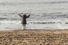 Enfant heureux se tenant près de la côte de l'océan photographie stock