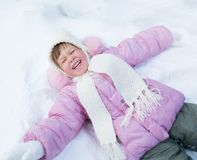 Enfant heureux se trouvant sur la neige en hiver extérieur Images stock