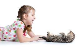 Enfant heureux se trouvant sur le plancher et jouant avec le chaton Photo libre de droits